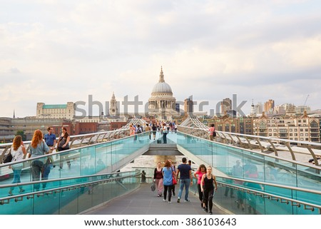LONDON - AUGUST 7: Millennium bridge with people walking and St Paul cathedral in a summer evening on August 7, 2015 in London. The footbridge crosses the river Thames.