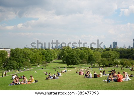 LONDON - AUGUST 8: Primrose hill top with London city view and people relaxing in the park on August 8, 2015 in London. Primrose hill is now one of most exclusive residential area in London.