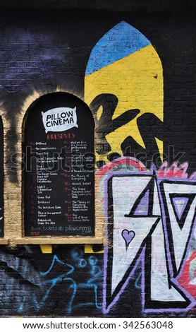 LONDON - AUGUST 1, 2015. Programme and painting on the Pillow Cinema wall at Pedley Street, Shoreditch in the Borough of Tower Hamlets, an area renown for its street art in east London, UK. - stock photo