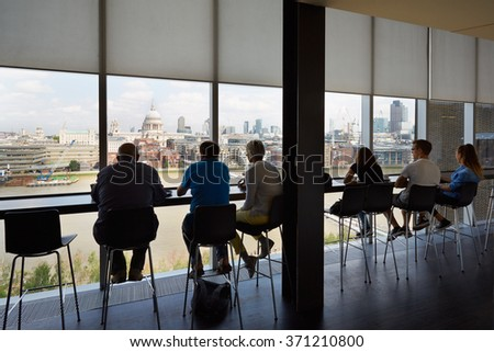LONDON - AUGUST 8, 2015: Tate Modern Art Gallery cafe interior with people and city view on August 8, 2015 in London, UK. Tate Modern is located in the former Bankside Power Station. - stock photo