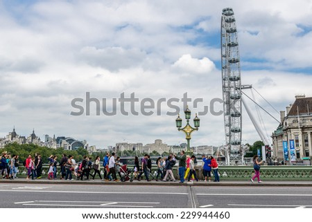 LONDON - AUGUST 27, 2014: Tourists cross the Westminster Bridge in front of the London Eye, Europe's tallest Ferris wheel on the South Bank of the River Thames, a famous tourist attraction - stock photo