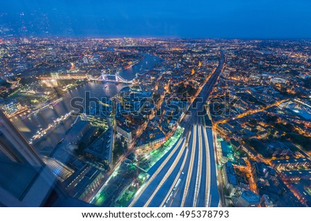 London Bridge Station aerial view at night. Transportation infrastructure with city skyline.