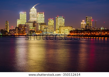 London Canary Wharf and Thames at night, corporate finance concept