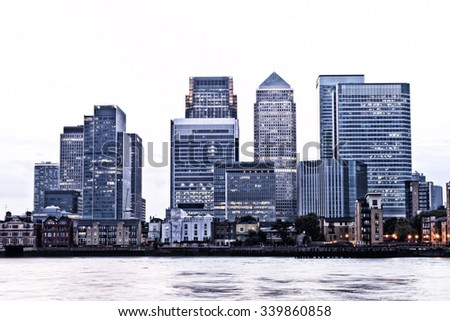 London Canary Wharf city financial district at twilight with sky faded to white - stock photo