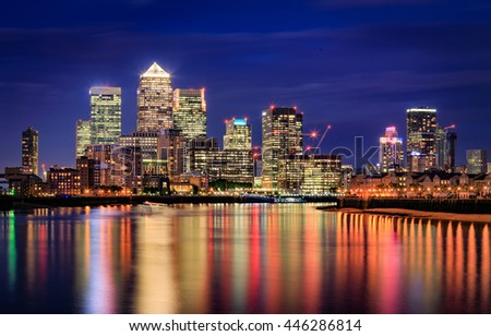 London, Canary Wharf in night with reflection in Thames water.