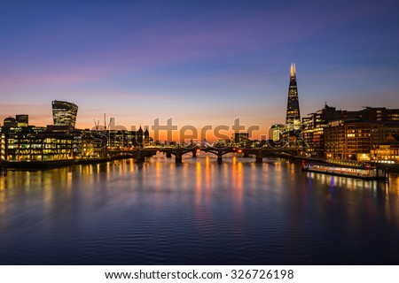 London cityscape during sunrise - river Thames with silhouettes of modern skyscrapers
