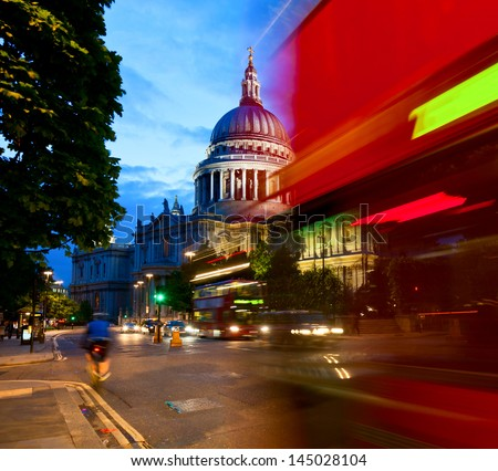 London cityscape with St Paul's Cathedral and moving Double Decker buses at night - stock photo