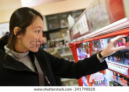 LONDON - DEC 12: A shopper browses a shelf in a Boots pharmacy on Dec 12, 2014 in London, UK. Founded in 1849 Boots has grown from a family business to a multinational employing over 120,000 staff. - stock photo