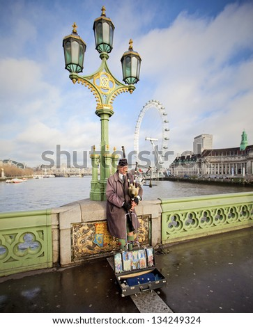 LONDON - DEC 21: Bagpiper musician on Westminster Bridge in front of the London Eye in the United Kingdom December 21, 2012 in London, England - stock photo