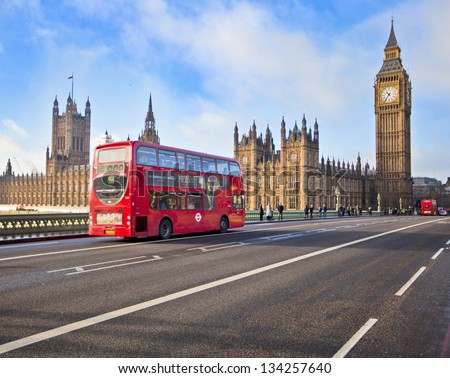 LONDON - DEC 21: Iconic London bus crossing Westminster Bridge in the United Kingdom December 21, 2009 in London, England - stock photo