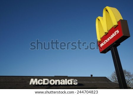 LONDON - DEC 13: McDonalds logo on blue sky background on Dec 13, 2014, London, UK. It is the world's largest fast food chain, over 31,000 restaurants worldwide, serve 58 million customers each day.