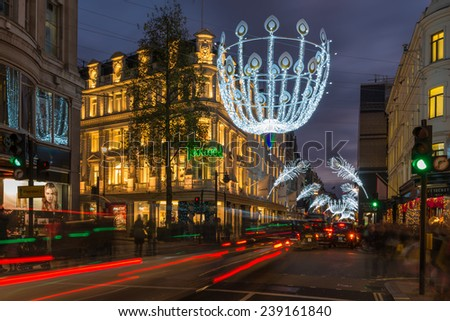 LONDON - DECEMBER 21st 2014: Christmas lights on New Bond Street. The already glamorous area has been given a glittering makeover for the Christmas season with sprays of peacock-inspired decorations. - stock photo