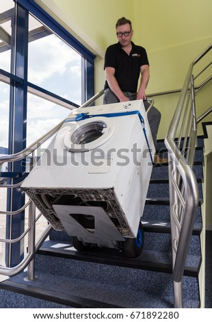 london, england, 02/02/2017 A man in an industrial warehouse lifting heavy items up stairs with a small industrial stair walking lifting style device.