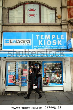 London, England - April 02, 2015: A man walking past a newsagent and tobacconist advertising Lebara Mobile communications services in London, England. Lebara Group was founded in 2001