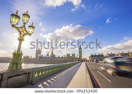 London, England - Big Ben and Houses of Parliament with traditional British black taxi on the move on Westminster Bridge