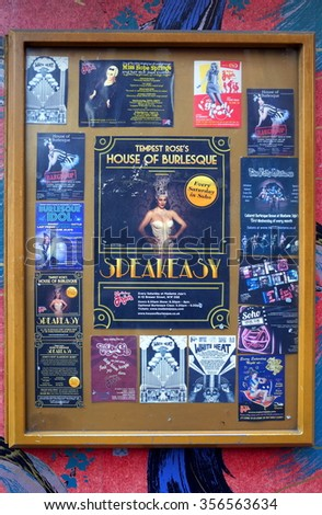 London, England - December 28, 2015: Glass billboard on a painted wall with posters and flyers advertising burlesque entertainment shows and DJ nights at venues in the Soho district of London, England - stock photo