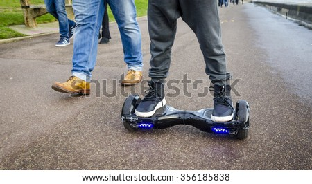 London, England - December 28, 2015: Person Riding a HoverBoard on a Public Footpath, They are now banned in all public places in the United |Kingdom.  - stock photo