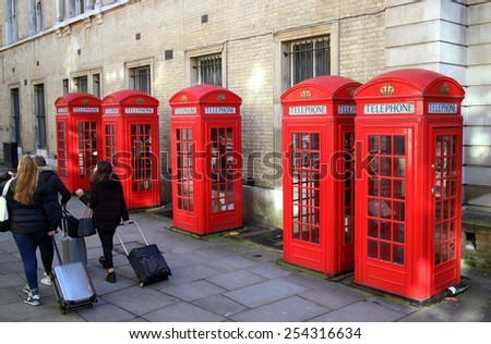 London,England - February 17, 2015: People with luggage walking by a row of red telephone boxes in London, England.  The K2 type model by architect Sir Giles Gilbert Scott was introduced in 1926 - stock photo