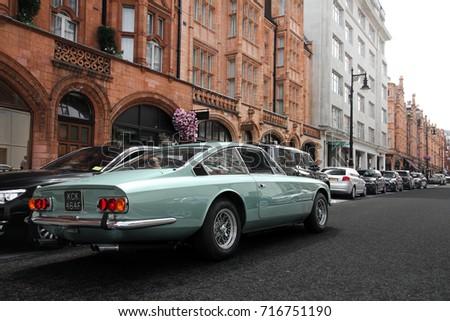 London, England - 17.06.17: Ferrari 365 GT 2+2 sports car cruising down one of Mayfair streets in central London. The aqua colored Ferrari is one of a few 4-seater models of the Italian brand.