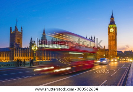 London, England - Iconic Red Double Decker bus in motion on Westminster bridge at dusk with Big Ben and Houses of Parliament at background - stock photo