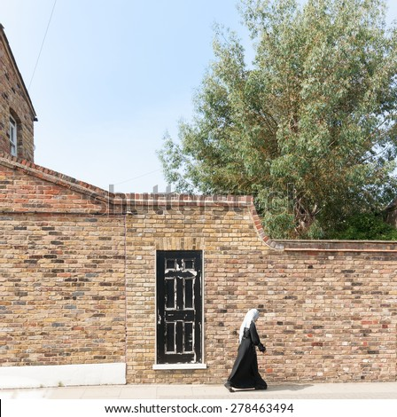 LONDON, ENGLAND - JULY 13; a lone Muslim woman in Bow East London dressed in black and white passes black and white door in brick wall on July 13, 2013 in London, England. - stock photo