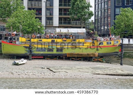 LONDON, ENGLAND - JULY 8, 2016: Beached boat-restaurant due to low tide of The Thames river in London, close to Vauxhall Bridge. - stock photo