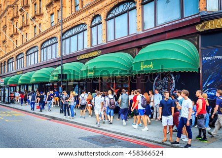 LONDON, ENGLAND - JULY 20, 2016. Exterior of Harrods department store in the Brompton Road, Knightsbridge showing shoppers passing by.