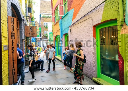 LONDON, ENGLAND - JULY 16, 2016.  Neals Yard with unidentifed people. It is a small alley in Covent Garden with colorful houses. It contains several health food caffes and values driven retailers. - stock photo