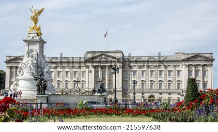 London, England - July 29th 2014: Tourists gather at the gates of Buckingham Palace and the base of the victoria monument. The flag flies to show the queen is in residence  - stock photo