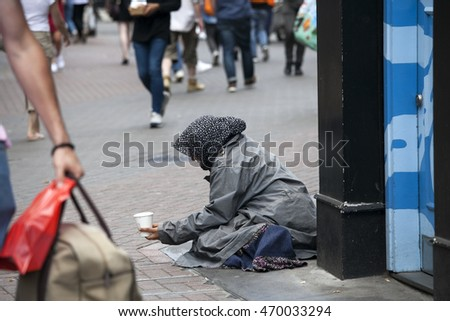 LONDON, ENGLAND - JULY 12, 2016:  The poor beggar woman sits on the pavement.