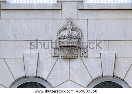 LONDON, ENGLAND - JULY 8, 2016: The Royal Cypher of King Edward VIII captured on a building facade in London and on permanent public display. It uses the Tudor Crown above the lettering. - stock photo