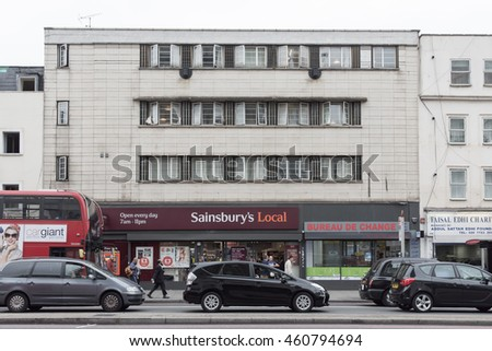 London, England - July 15, 2016: Traffic queuing on the Edgware Road beside run-down buildings and a Sainsbury's Local supermarket near Paddington in central London.