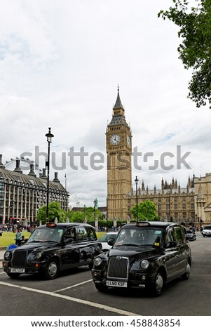 LONDON, ENGLAND - JULY 8, 2016: Two iconic black cabs in front of Big Ben tower. With 96.3 meters high, it is one of the most important attraction and a symbol of London. - stock photo