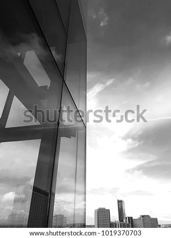 LONDON, ENGLAND, JUNE 15TH 2016: Black and white exterior view of a glass panel on office block in Croydon, with blue sky and clouds