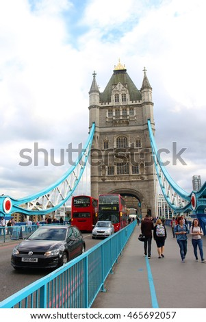 LONDON, ENGLAND - JUNE 17, 2015: Traffic and pedestrians crossing under the towers of the Historic London Bridge over the River Thames  in London England