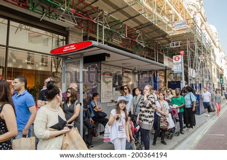 LONDON, ENGLAND - JUNE 21, 2014: Travellers waiting at a bus stop made of toy Lego bricks.  The sculpture was created from the toy bricks outside Hamley's toy shop to mark 200 years of London buses.  - stock photo