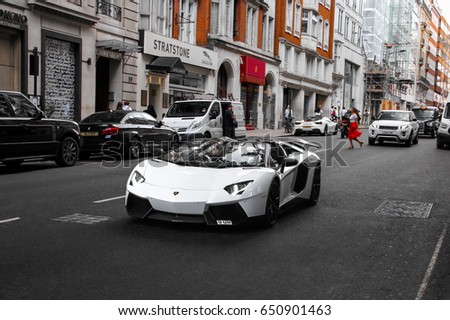 London, England - 24.05.2017: Lamborghini Aventador Roadster supercar driving in Mayfair district in London. Sports cars like this are very common in central London.