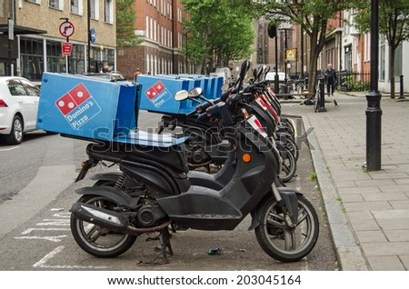 LONDON, ENGLAND - MAY 17, 2014: A row of mopeds operating for the Domino's Pizza takeaway chain parked in Westminster, London. - stock photo