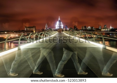 LONDON, ENGLAND - MAY 10, 2012: A slow motion of a man who is  walking cross Millennium Bridge which crossing the River Thames with dome of St. Paul's Cathedral as a background at night time