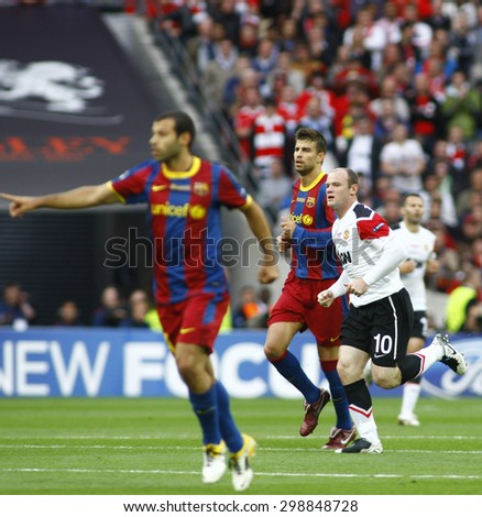 LONDON, ENGLAND. May 28 2011: Barcelona's defender Gerard Pique and Manchester's forward Wayne Rooney during the 2011UEFA Champions League final between Manchester United and FC Barcelona - stock photo