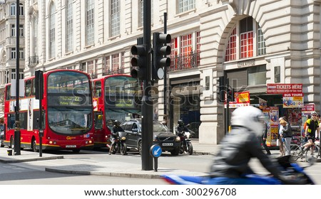 LONDON, ENGLAND - MAY 30: Double -deckers and motorcyclists near Piccadilly Circus on May 30, 2015 in London - stock photo
