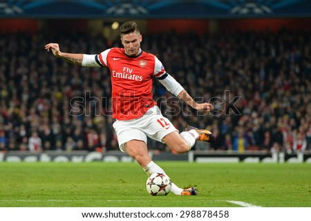 LONDON, ENGLAND - Nov 26 2013: Arsenal's Oliver Giroud slips as he takes a shot at goal during the UEFA Champions League match between Arsenal and Olympique de Marseille, at The Emirates Stadium - stock photo