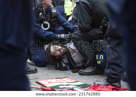 LONDON, ENGLAND - NOVEMBER 19: Students take part in a protest march against fees and cuts in the education system on November 19, 2014 in London, England. Police detains student - stock photo