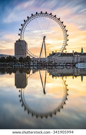 LONDON, ENGLAND - NOVEMBER 8,2015 : The London Eye on the South Bank of the River Thames at  sunrise  in London, England. Vertical composition. - stock photo