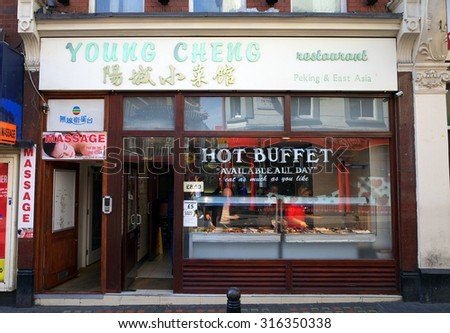 London, England - Sept 09, 2015: People at the buffet counter in the window of a Chinese restaurant situated next door to a massage parlour in Chinatown, London, England.