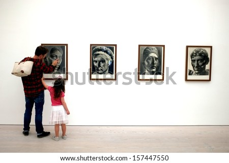 """LONDON, ENGLAND - SEPTEMBER 29, 2013: Father and his daughter view the artworks in Saatchi Gallery's """"Paper"""" exhibition in London. - stock photo"""