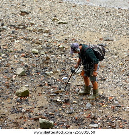 London,England - September 22, 2009: Man using a metal detector at low tide on the River Thames in London, England. A permit is required and any finds must be reported by law under the Treasure Act. - stock photo