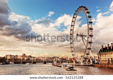 London, England the UK skyline in the afternoon. The London Eye on River Thames - stock photo