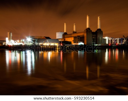 London, England, UK - July 14, 2009: The derelict ruins of the iconic Battersea Power Station are reflected in the waters of the River Thames at night.