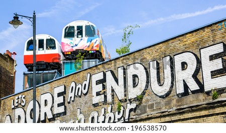 LONDON, ENGLAND, UK - MAY 4, 2014: Graffiti on the Village Underground wall and old colorful train wagons behind it in Brick Lane area. Urban art in this area attracts tourists from all over the world - stock photo